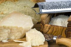 Grated Grana Padano. And cut bread on a table Royalty Free Stock Images