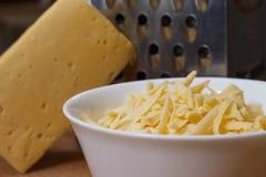 Grated holländsk ost i en platta på ett bräde Arkivbilder