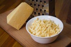 Grated holländsk ost i en platta på ett bräde Arkivfoton