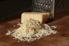 Grated italian parmesan cheese on wooden chopping board with a block of parmasan and a grater in the background. Close up photo. With selective focus stock images