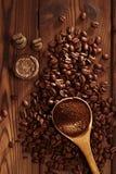 Grated kaffe i sked på grillad bakgrund för kaffebönor Royaltyfria Foton