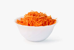 Grated morötter i en vit kopp Arkivbild