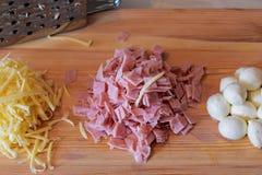 Grated ost, huggen av skinka, bollar av mozzarellaen och rivjärn på träbakgrund Royaltyfri Fotografi