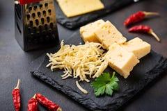 Grated ost kritiserar på brädet royaltyfri foto