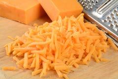 Grated ost på en skärbräda Arkivbild