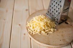 Grated ost på ett träbräde Arkivbild
