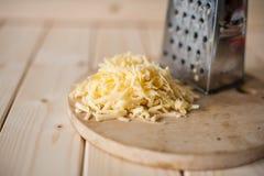 Grated ost på ett träbräde Fotografering för Bildbyråer