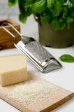 Grated Parmesan. Cheese with basil in the background Royalty Free Stock Images