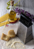 Grated parmesan cheese, bottle of olive oil and metal grater on Royalty Free Stock Photo