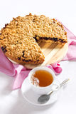 Grated pie with a cup of tea. On the table and decorated with pink Stock Photography