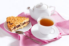 Grated pie with a cup of tea. On the table and decorated with pink Stock Image