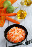Grated radish and carrot. Carrots and radishes in a black bowl on a wooden table Royalty Free Stock Images