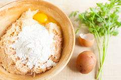 Grated raw potatoes, eggs and flour in a large bowl Stock Images