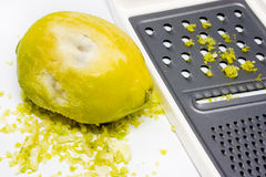 Grated yellow lemon rind. Grated lemon rind with grater stock photo