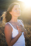 Grateful for being. Beautiful young woman with her hands on her chest looking gratefully towards the sky stock photography