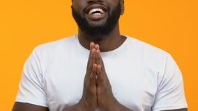 Grateful black man praying on yellow background, thanksgiving ritual, religion. Stock footage stock footage
