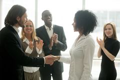 Grateful boss handshaking promoting african businesswoman congra. Tulating with career achievement while colleagues applauding cheering successful worker Royalty Free Stock Images
