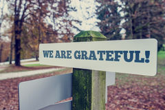 We Are Grateful. Concept with an angled signboard with the words on a rustic wooden pole in an autumn landscape, with a vintage style filter effect Stock Images