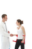 Grateful patient thanking doctor. Grateful young disabled women patient on crutches thanking her doctor by shaking his hand Royalty Free Stock Photos