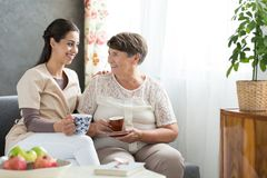 Senior lady serving tea. Grateful senior lady serving tea to a helpful nurse visiting her at home after hospitalization Royalty Free Stock Photography