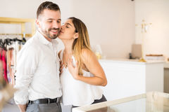 Grateful woman kissing her husband. Pretty young brunette kissing her husband on the cheek after getting a new necklace for her at a jewelry store stock photos