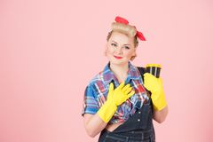 Gratefulness housewife holding craft cup. Portrait of thankfulness woman in latex gloves with cup of coffee in pin-up style. royalty free stock photos