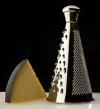 Grater and cheese wedge Royalty Free Stock Photography