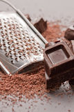 Grater and chocolate. Grating dark chocolate against grater stock image