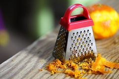 Grater zest of citrus fruit and on wooden table stock photography