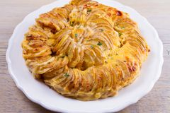 Gratin картошки на белой плите Испеченные куски картошки с сметанообразным соусом Стоковое фото RF