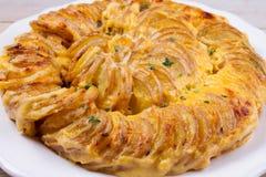 Gratin картошки на белой плите Испеченные куски картошки с сметанообразным соусом Стоковое Фото