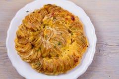 Gratin картошки на белой плите Испеченные куски картошки с сметанообразным соусом Стоковая Фотография RF