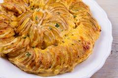 Gratin картошки на белой плите Испеченные куски картошки с сметанообразным соусом Стоковые Фотографии RF