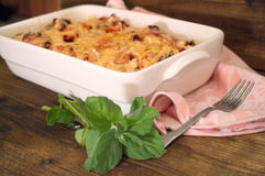 Gratin in casserole. Gratin in white casserole in wooden background royalty free stock photos