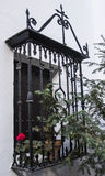 Gratind with flowers. Grid with wrought iron with different details on a typical Andalusian window Stock Photo