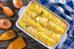 Gratinerade Dauphinois, potatisar som är förberedda för att grilla i en panna Arkivbilder