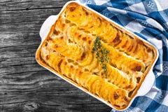 Gratinerade Dauphinois, potatisar som bakas i en stekhet maträtt, närbild royaltyfri fotografi