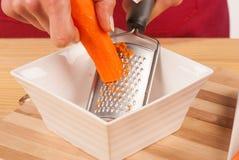 Grating carrots Stock Photos