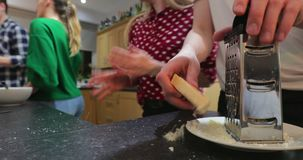 Grating cheese in the kitchen. Close up shot of cheese being grated in preparation for a meal at a student home stock footage