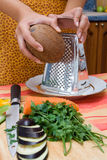 Grating coconut. In the kitchen Stock Image