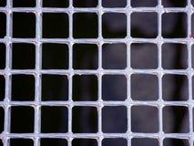 Grating metálico de prata dos quadrados em um fundo preto Imagens de Stock Royalty Free