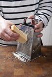 Grating Parmesan Cheese. Female chef grating parmesan cheese, preparing italian food Royalty Free Stock Photography