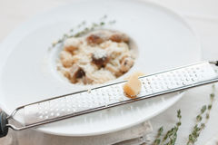 Grating parmesan cheese for italian cuisine dish, wild mushroom risotto Stock Images