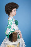 Gratiosity and elegance. Elegant 18th century lady wearing vintage fashion clothing and leaning on books Stock Photos
