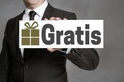 Gratis auf Deutsch kostenlos wird Schild vom Geschäftsmann gehalten Stockbild