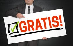 Gratis in german free of charge poster is held by businessman.  royalty free stock photos