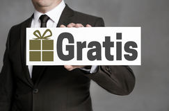 Gratis in german Free of Charge shield is held by businessman Stock Image