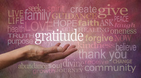 Gratitude Attitude. Female hand outstretched with palm up and the word Gratitude hovering above with a stone effect background covered in different colored and Royalty Free Stock Photos