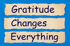 Gratitude Changes Everything. Written in old torn paper on blue background. Politeness, thanks, gratitude concept royalty free stock photos