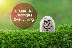 Gratitude changes everything. The text gratitude changes everything with stone smile happy face on green moss and sunshine light background stock photo